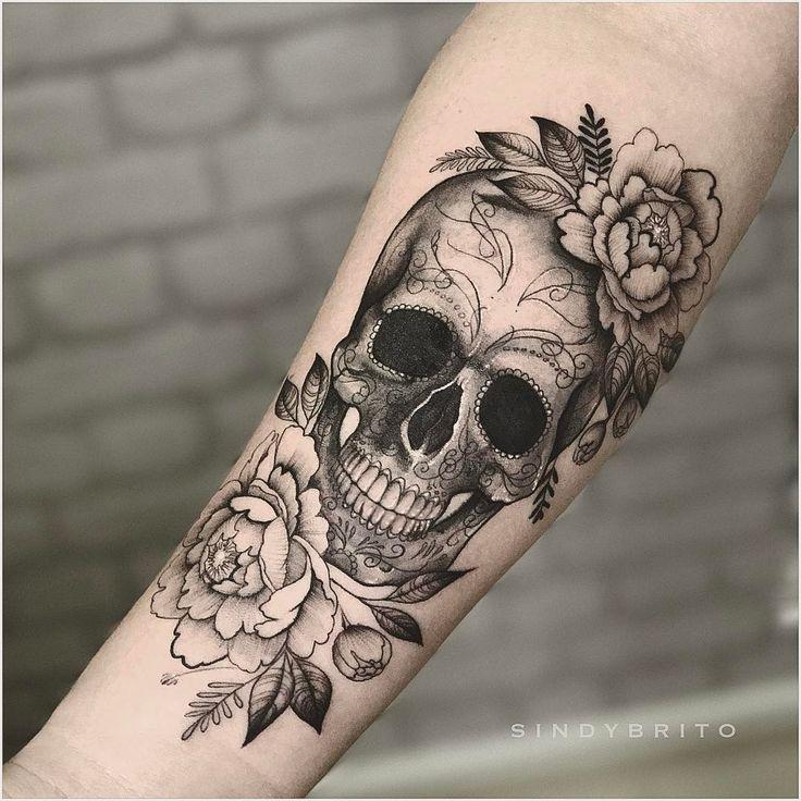 Tatuagem criada por Sindy Brito de Brasília.  Caveira em preto e cinza com flores no braço.