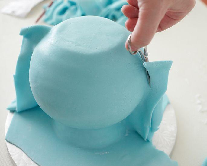 Use uma tesoura para cortar o excesso da pasta para baixo,ou então, segue a curva da bola bolo. Em seguida, mergulhe o pincel na água e umedecer o interior da costura. Feche a pasta de volta juntos e gentilmente apertar a costura com vocês dedos para fazê-la ficar juntos. Em seguida, use a tesoura para cortar novamente o cume de fondant mais perto da forma do bolo. Use o dedo para esfregar a costura para torná-lo o mais plano possível.