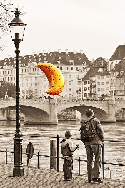 "The moon balloon by Tambako the Jaguar on Flickr. ""A son and his father at the looking at the Rhine river in Basel, during the Herbstmesse (autumn fair). I was there on Sunday and saw the scene while walking. I couldn't resits to take the picture, because it was looking unique, with the framing as well. I converted it to sepia but the balloon which retained its original color."""
