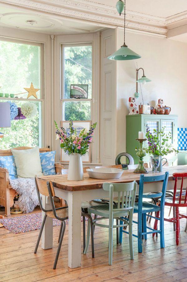 Comedor muy colorido con mesa de madera de patas gruesas blancas y cubierta de madera color natural. Las sillas son de madera y colores verde claro, azul y roja, para complementar con sillas de estructura metálica y asiento y respaldo de madera barnizada.