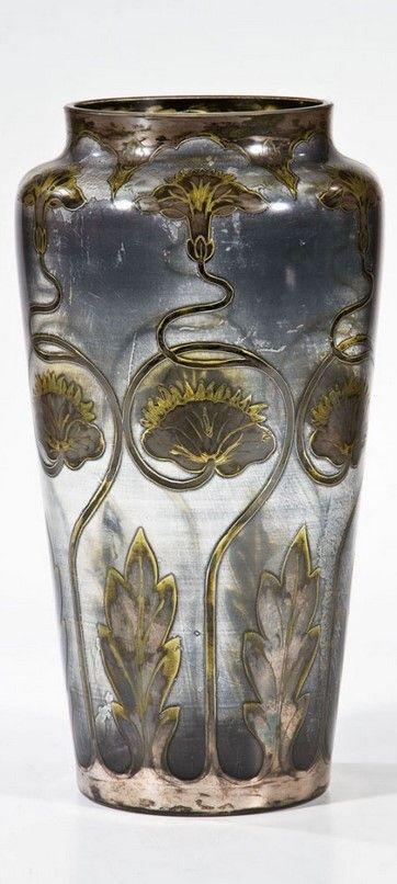 Vase mit Seerosen Carl Goldberg, Haida, um 1900 Farbloses Glas mit Ätzung, Silbergelbbeize und Silbermalerei. Umlaufend sechsfach rapportierender Dekor: Blüten, Knospen und Blätter der Seerose. Binnenzeichnung in Nadelätzung. Teils berieben. H. 30 cm