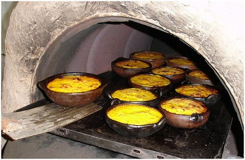 Pastel de choclo: cooked ground beef, chicken, eggs, seasonings, topped with cream of corn then baked in clay bakeware.
