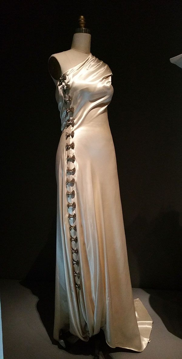 "Madeleine Vionnet (French, 1876-1975); EVENING DRESS, 1936, haute couture, Machine-sewn white cellulose acetate satin, hand-finished seams and hems with hand-attached silver metal clasps and bow-shaped silver metal and clear rhinestone clips, ""Everything came from my head. Bias came from my head, maybe because everyone made dresses that flowed in the same direction. But I saw that if I turned the fabric on an angle, it gained elasticity."""
