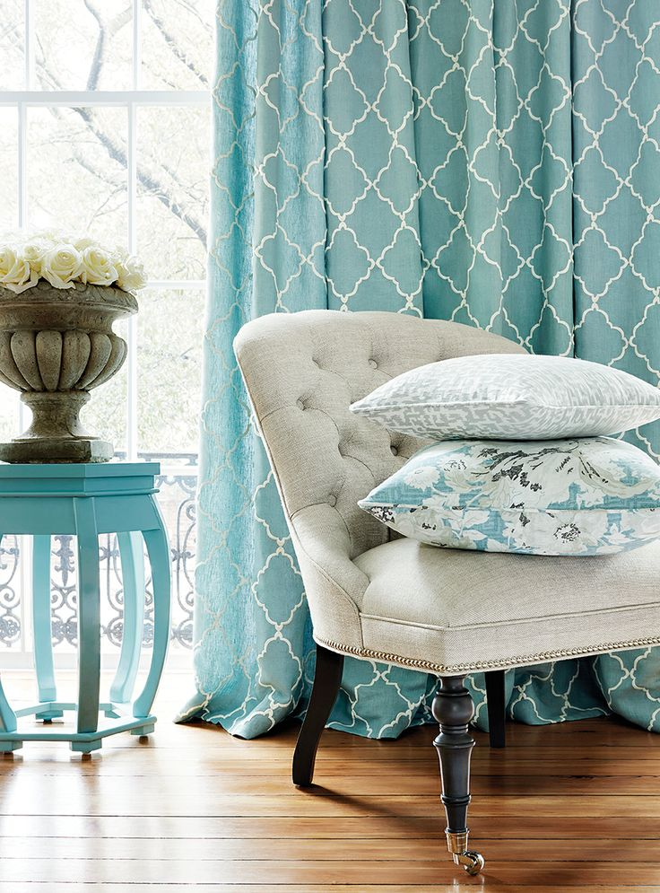 Lovely blue draperies with tufted chair and cute pillows.