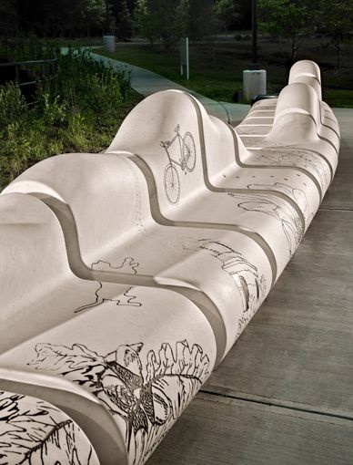 Around Town, Chapel Hill, NC. The seat back is a sculpted, undulating elevation that references the region's rolling topography. Engraved into the bench are images from the area, such as local architecture, wildlife, and green transport - bikes
