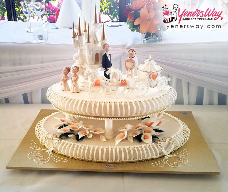 2 tier oval shaped wedding cake on pillars decorated with a pastillage castle, horses and carriage, and couple figurines.