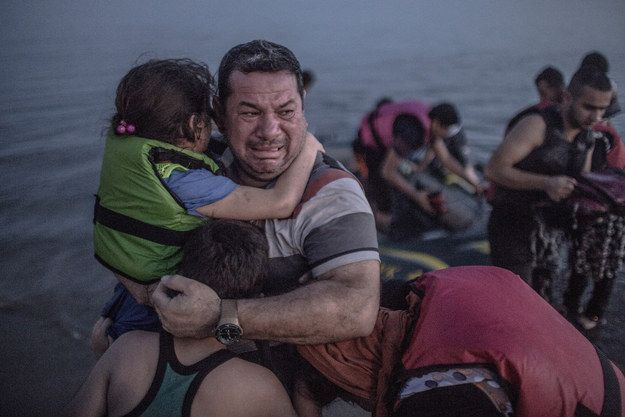 The story was accompanied by a gallery of photos, along with this image, which showed a Syrian man in tears, while holding on to his children after getting off a boat on the Greek island of Kos. | The Story Behind The Heartbreaking Photo Of A Syrian Refugee Family - BuzzFeed News