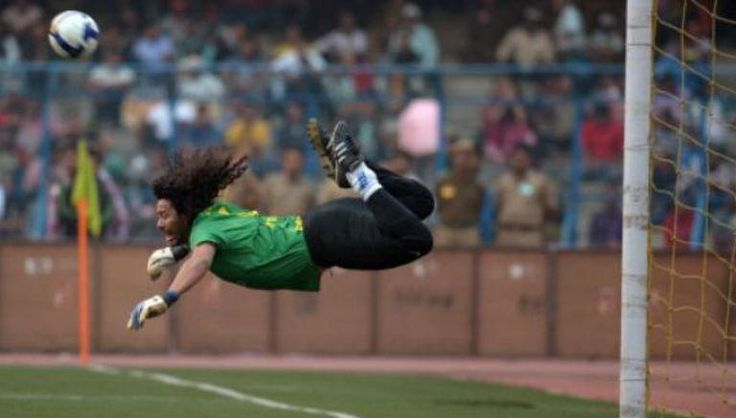 En esta imagen se puede ver la jugada que va a realizar el portero , como se tira y se sostiene en el aire para impactar el balón , se nota este hombre decidido y un poco cansado.