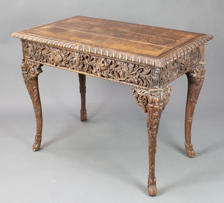 """Lot 850, A Georgian heavily carved oak centre table fitted a frieze drawer, raised on carved cabriole supports 29"""" x 28 1/2""""w x 23""""d, est £200-300"""