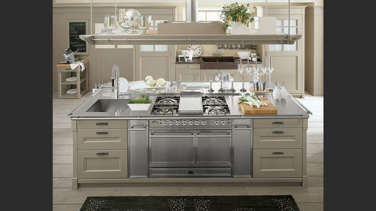L%u2019isola dispone di piano in acciaio satinato provvisto di tagliere, canale attrezzato, piano cottura con fry-top, blocco cottura dotato di due forni.