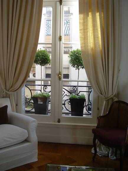 Love the simple cream curtains with tie backs and the matching ornamental pots on the balcony