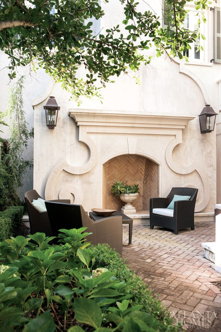 """We wanted the fireplace sitting area to draw people out for picnics or cocktails,"" Spitzmiller adds. Cast-stone mantel and face veneer designed by Spitzmiller and produced by Cutting Edge Stone. The furniture is by Janus et Cie. ""Every way you approach the house you get a beautiful view of the courtyard,"" says designer Susan Massey."