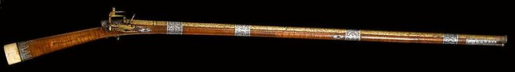 A PERSIAN/CAUCASIAN IVORY-MOUNTED FLINTLOCK RIFLE, EARLY 19TH CENTURY The steel barrel wholly decorated with gold overlay floral motifs, clasped to the forestock by applied niello mounts, gold overlay to the trigger and trigger plate, niello band of palmettes at ivory butt plate.