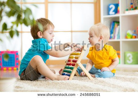 children boys play with abacus toy indoors - stock photo
