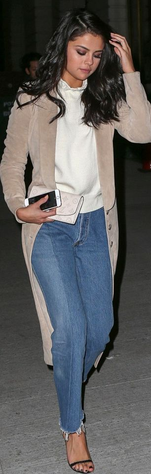 Who made Selena Gomez's black sandals, blue skinny jeans, wallet, white sweater, and tan coat?