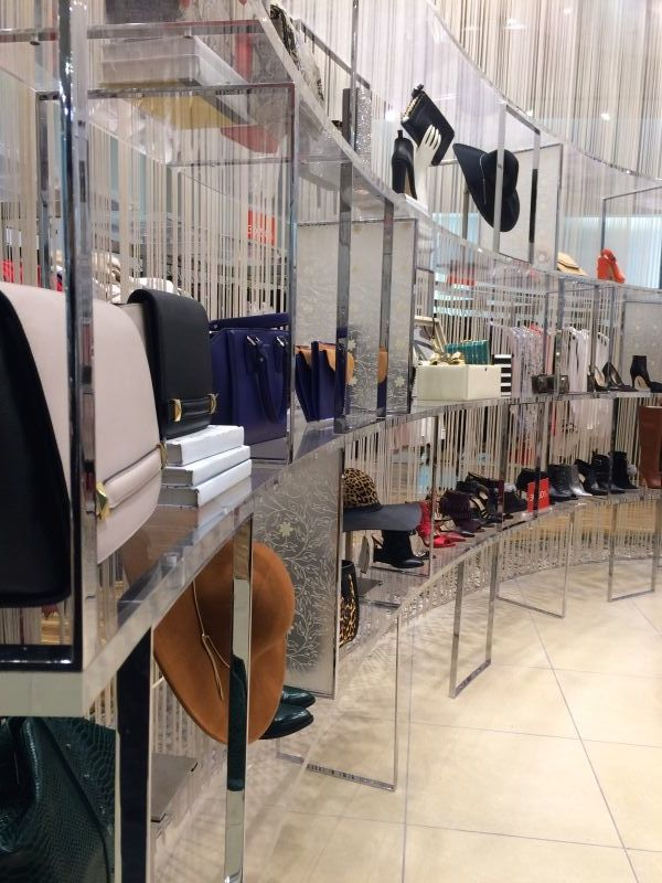 there are shoes and bags on the shelf, and there is a bench people can sit down and try shoes. this part is before the fitting room. when people chose the clothes they want to try, they also can look around the shoes and bags to make a complete look. putting merchandising on the shelf can give people good view to chose.