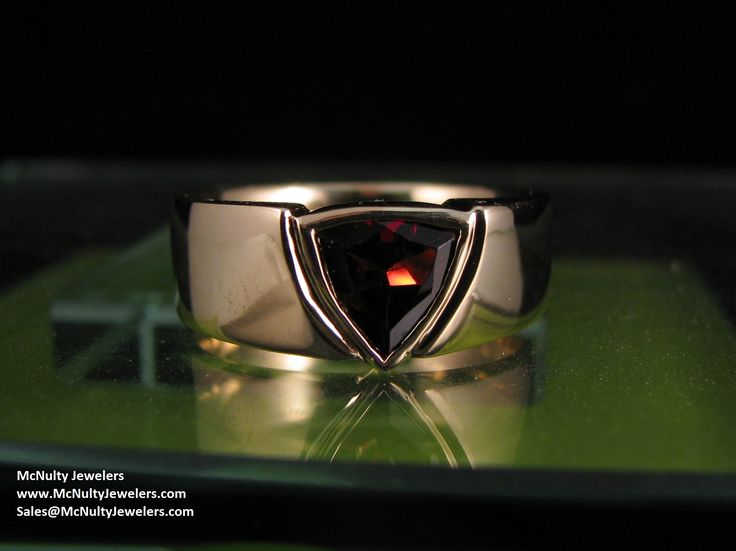 This simply designed men's ring features a trillion cut Garnet set in yellow gold.  McNulty Jewelers original design