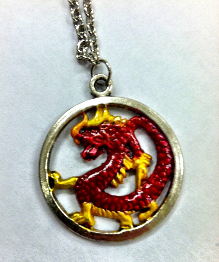 This is a Komodo dragon that has a red body, yellow spikes and legs, and that breaths orange fire. The dragon swims inside a silver plated ring and hangs from a thin silver plated chain that has a lobsterclaw clasp. He sold for $35.00.