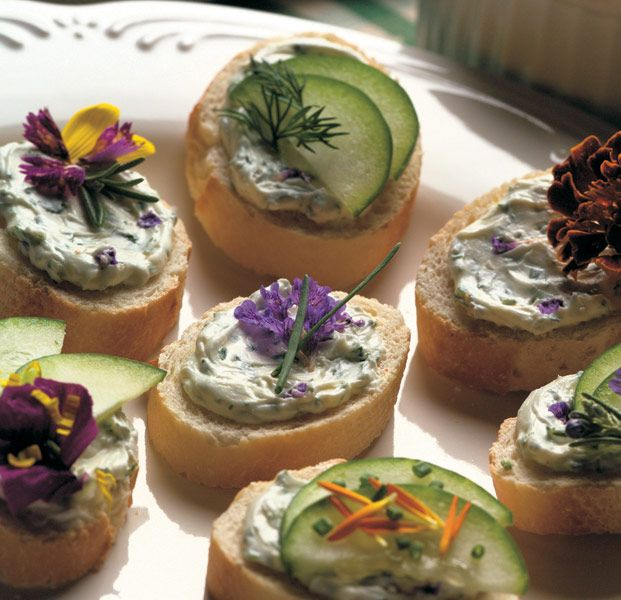 Tea sandwich bites topped with cream cheese mixed with herbs de Provence and garlic, garnished with cucumber slices and edible flowers