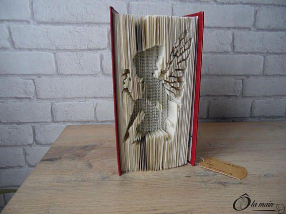 La collection A Livre Ouvert est une série de livres doccasion transformés en objets de décoration via plusieurs techniques (découpage, pliage ou décou-pliage). Chaque page est découpée et/ou pliée à la main pour donner vie à un motif.  Le modèle Féérie est un livre découpé et plié pour représenter la silhouette dune jolie fée. Le livre possède une magnifique couverture rouge et or. VENDU SEUL