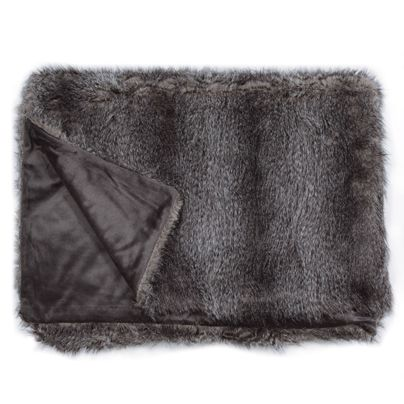 Textured fur throw rugs add warmth to cold leather couches in winter.