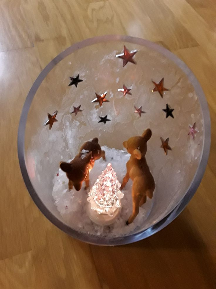 Ich habe ein großes Glas von innen mit Eisspray eingesprüht und trocknen lassen. Die Rehe und die Sterne sind mit Heißkleber aufgeklebt worden. Dann habe ich künstlichen Schnee reingeschüttet und den Tannenbaum (mit Batterie) reingestellt.