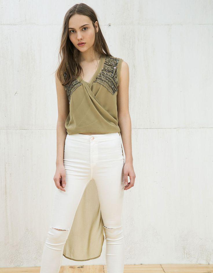 Blusa assimétrica com nó e bordados. Descubra esta e muitas outras roupas na Bershka com novos artigos cada semana