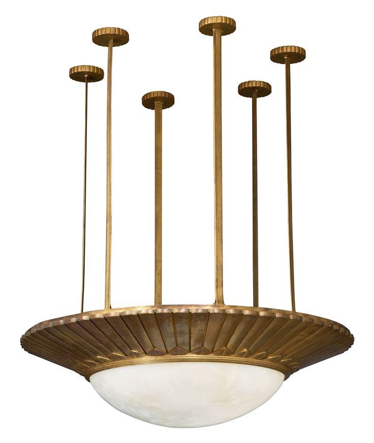 EMILE-JACQUES RUHLMANN (1879-1933) SUSPENSION, VERS 1925 La coupe circulaire en albâtre, sertie dans une monture rayonnante en bronze doré à godrons et motif de feuillage stylisé, retenue par six tiges rainurées imitant des lanières de cuir, fixées au plafond par six cache-bélières circulaires godronnés Hauteur : 123 cm. (48 3/8 in.) ; Diamètre : 106 cm. (41¾ in.) Signée RUHLMANN sur le pourtour extérieur de la monture