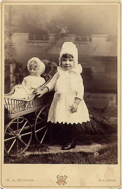 Antique photo of a little girl with her doll in a pram.