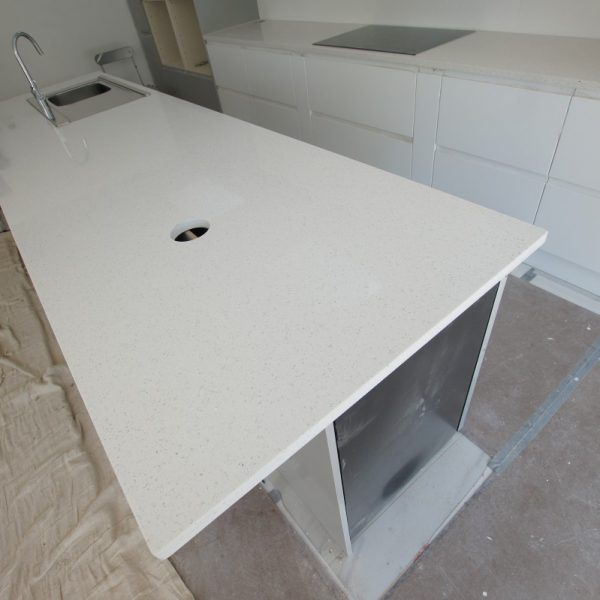 This is the Bianco Stella. We were very lucky and had the pleasure in working with James Degale to complete his parent's kitchen project. The Bianco Stella is a white style quartz with large mirror pieces running throughout.