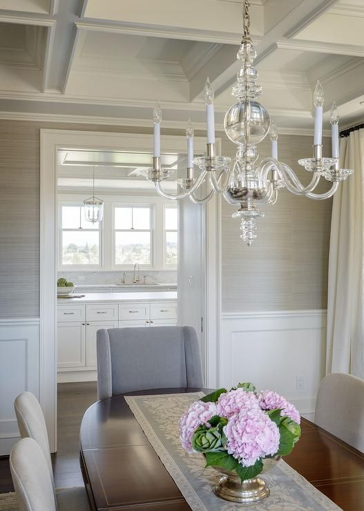 white on the bottom light gray on the top  covered with wainscoting on the lower half and gray grasscloth on the upper half and ivory curtains hang in the corner dining room in this beautiful transitional dining room.
