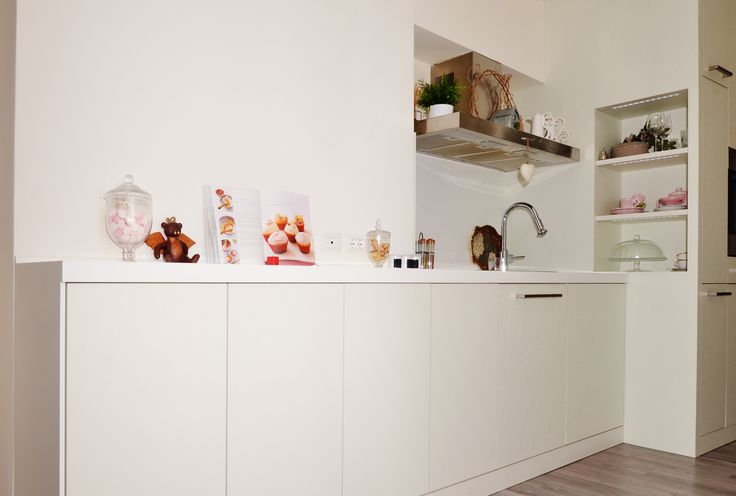 Linear kitchen furniture with column unit, oven, refrigerator and shelves. Corian top, color cameo white. Doors and niches built with a special custom structure, coated in white laminate with decorative background.