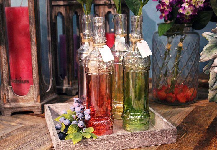 #Bottiglie in vetro colorato con bacche.