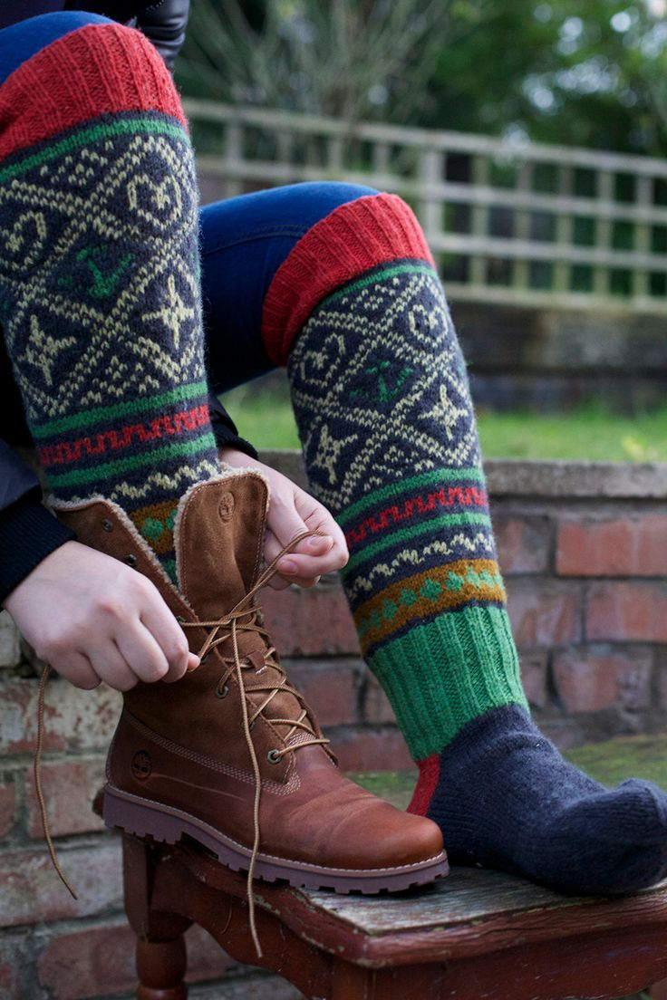 Knee high black knitted socks with Scandinavian ornaments for unisex adults.