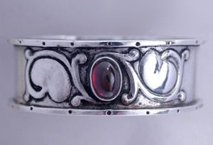 Guild of Handicraft. Arts and Crafts silver napkin ring set with a central cabochon garnet.