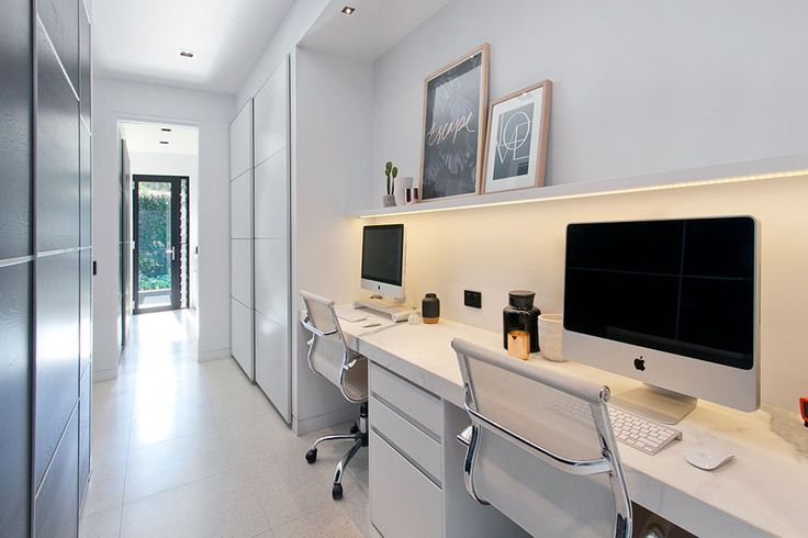 With enough room for two, this large desk sits below a small floating shelf with hidden lighting, while the long white hallway provides the perfect space for a tucked-away home office.