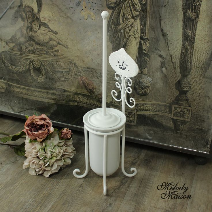 White 'Le Bain' Toilet Brush and Holder Perfect for a vintage bathroom with little plaque detail with the word 'Le Bain' and bath tub motif With a white ceramic holder in a white metal frame With scrolled detailing on the stand Toilet brush included with metal handle