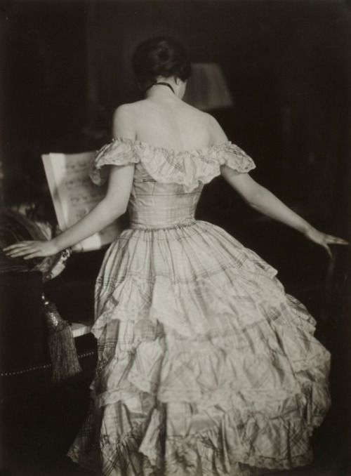 A woman standing by a grand piano, wearing a stunning ruffle dress with bare shoulders, XIX century.