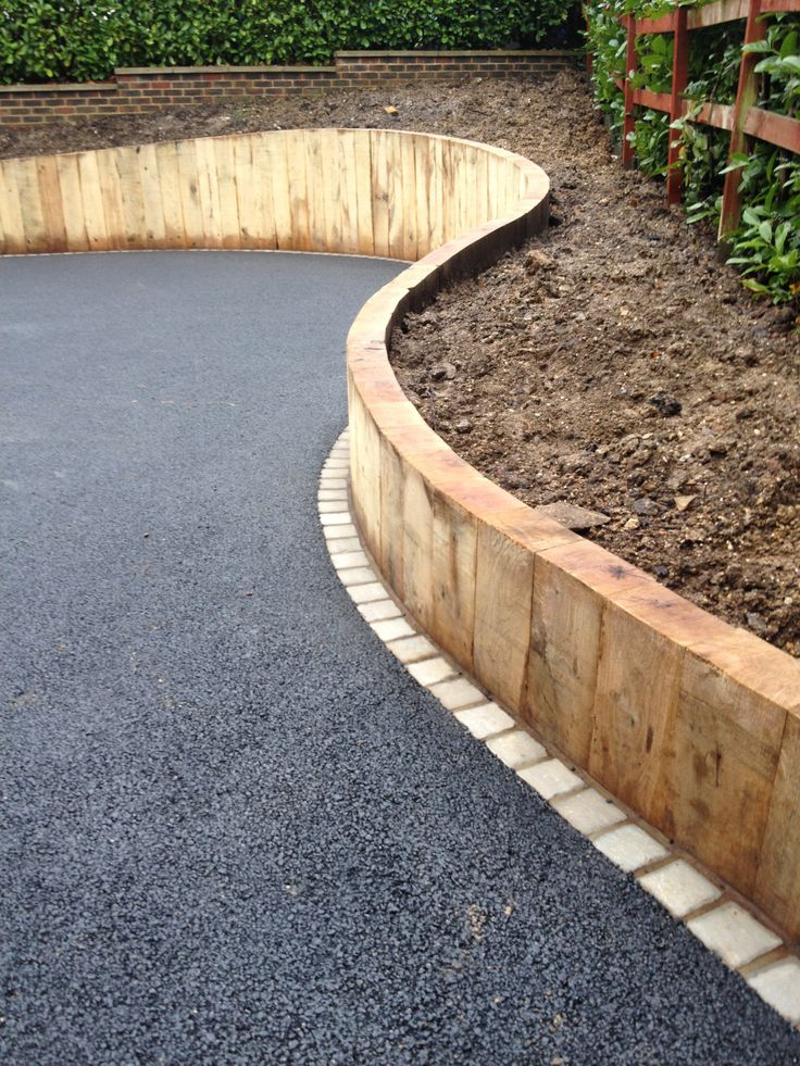 An alternate option to gabion, and probably less expensive is to use sleepers as a retaining wall on the drive. It ties in with the oak cladding on the house, the stone edging ties in with the sandstone paving and the tarmac gives a contemporary feel.