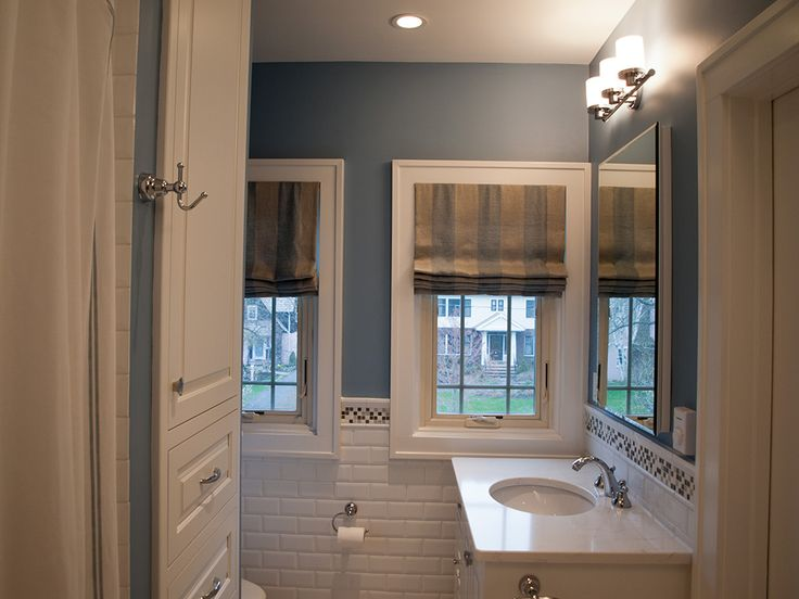Images Photos Custom roman shades and blue painted walls add depth to the mostly white master bathroom