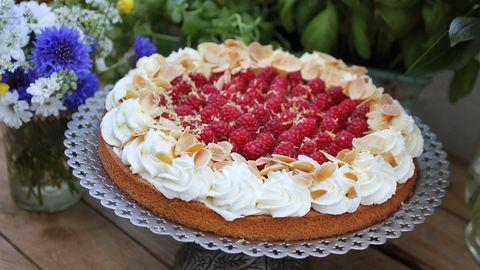 fin tårta med spritsad grädde pch hallon på fat, blommor i bakgrunden