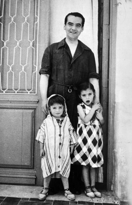 Il poeta e drammaturgo spagnolo Federico García Lorca posa all'ingresso della sua casa di Granada con le nipotine Conchita e Tica, figlie della sorella Conchita. Granada, maggio 1935