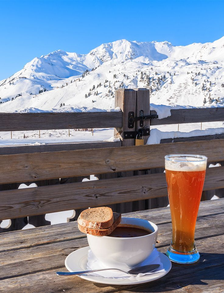 Glass of cold beer and hot soup on wooden table of mountain hut in Obertauern, Austria. Obertauern is one of the best ski resorts in Austria.