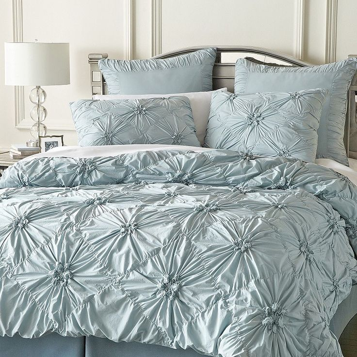 A celestial blue enhances the calming effect of this ruched bedding that gathers into a floral pattern on a field of diamonds