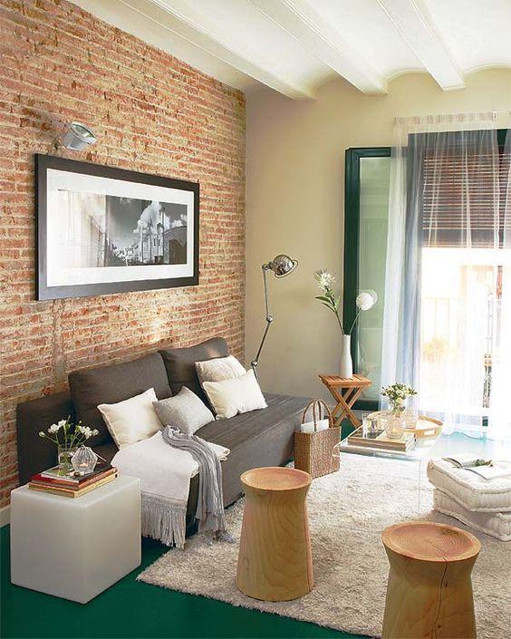 Sala de estar super aconchegante, com parede de tijolinho, tapete fofinho, quadro preto e branco e banquinho de madeira.