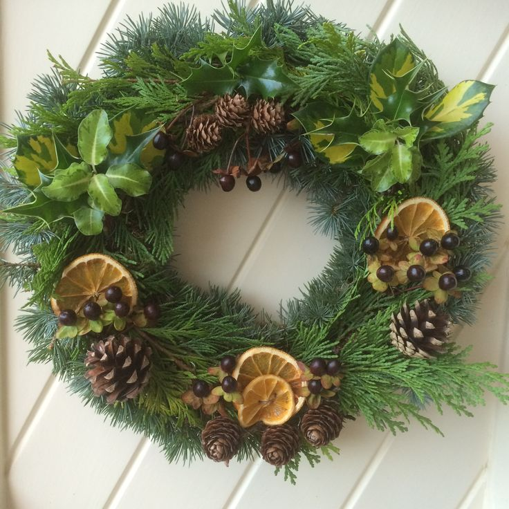 Catherine Duncan's wreath is made using moss from her garden along with conifer, holly, pittosporum and hypericum berries. With blue cedar, pine cones and dried orange slices.