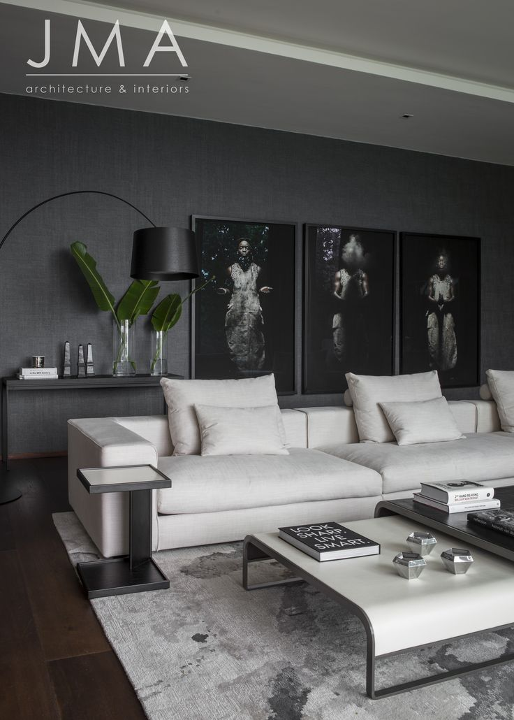 Grey lounge with artwork wall, on textured wallpaper.