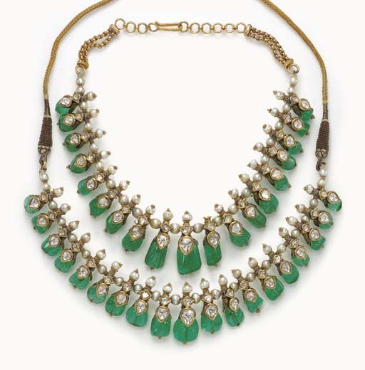 A PAIR OF DIAMOND, EMERALD BEAD AND ENAMEL INDIAN NECKLACES The first necklace designed as a series of graduated emerald beads, each set to the front with a foil-backed table-cut diamond, to the cultured pearl inner band, joined by adjustable silk cords; the second of similiar design, joined by a twin fancy link gold chain, 14¼ ins., both mounted in gold