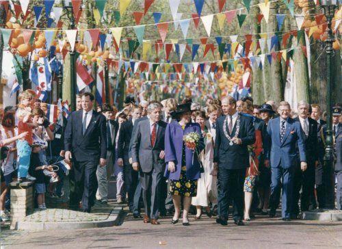Koninginnedag. Koningin Beatrix en de koninklijke familie op bezoek in Vlieland Nederland 30 april 1993. Foto: De koninklijke familie wandelt in gezelschap van de burgemeester door de Dorpsstraat die van het begin tot het eind met vlaggen is versierd.