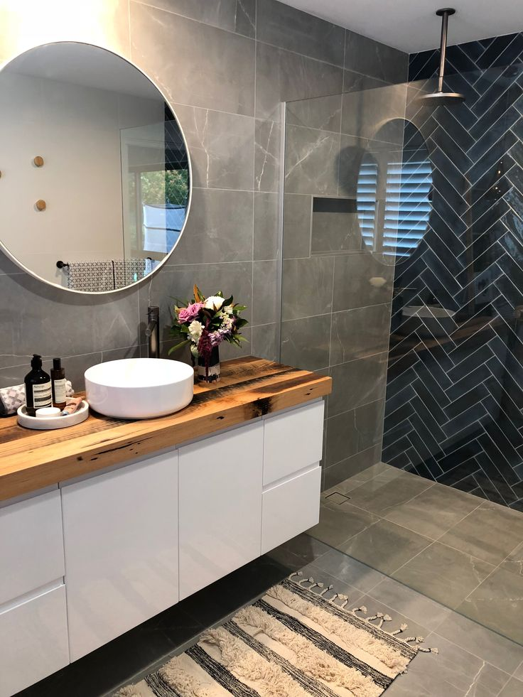Herringbone deep sea-blue feature tiles are a showstopper paired with gun metal finish tap wear and a recycled timber vanity top.